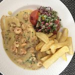 Beautiful prawns and fish in a creamy sauce with chips and salad.