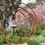 """Ribbons"" by Manning Sculptures, with weeping cherry tree in the background"