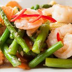Prawn and Asparagus stir fry. King prawns flash-fried with baby corn and green beans.