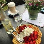 Waffel mit Erdbeeren und Sahne. Im Hintergrund eine Holunderblütenschorle und ein Latte Macchiat