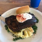 Blackened New York Steak topped with herbed creme fraiche, served with sautéed rapini and mashed