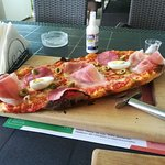 This is their classic pinsa. It is served on a wooden plate and a pizza cutter, and I find it ex