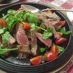 Tagliata di vitello, cotta alla perfezione, servita con pomodorini e insalata, scelta che non co