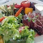 Magret de canard accompagnement salade mixte et légumes.