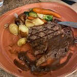 Rib steak with peppercorn gravy, fingerling potatoes and seasonal veggies with a roasted onion.