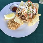 Prawn Pad Thai served in an edible basket. Chilli flakes and peanuts on the side