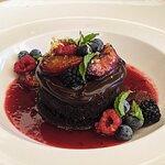 De cacao: torta húmeda de chocolate con frutos rojos y salsa de ciruelas