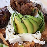 avocado toast con albóndigas de berenjena acompañado de ensalada y queso oaxaca