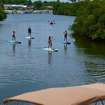 .as seen from our waterfront table, the stand -up Paddleboarders enjoy our Paradise on the Intra