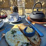White fluffy omelet with sourdough bread toasted and a pot of Masala Chai for two.