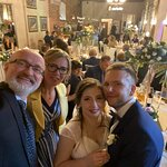 Happy couple with their guests during the wedding reception in