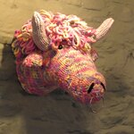 A knitted cow on the wall