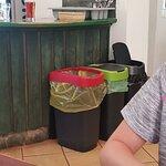 Trash cans next to food at the bar.