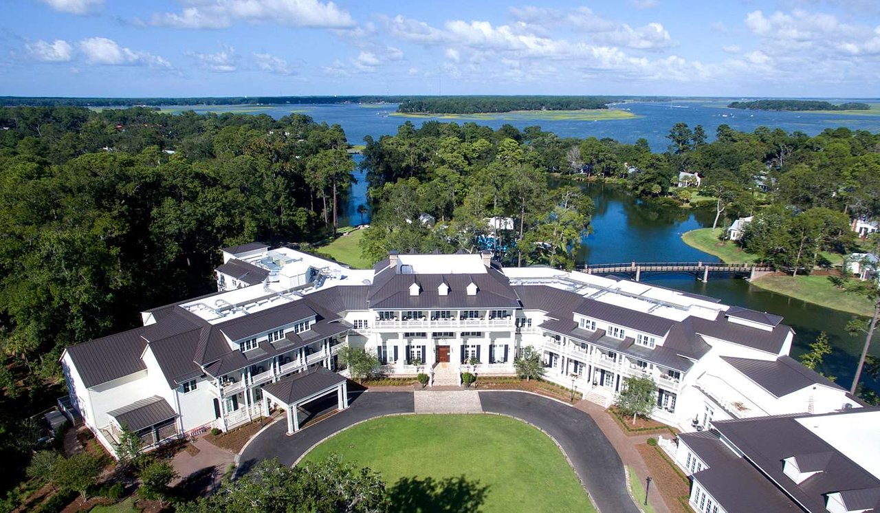 U-shaped 3 story white buildings of a resort overlooking lakes and gardens.