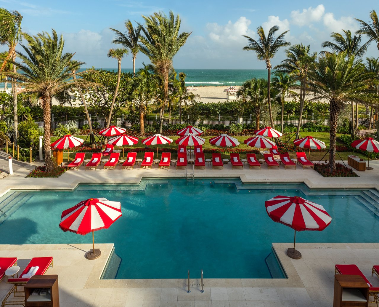 Hotel pool with red chaise lounge and red & white candy-cane striped umbrellas all around it.
