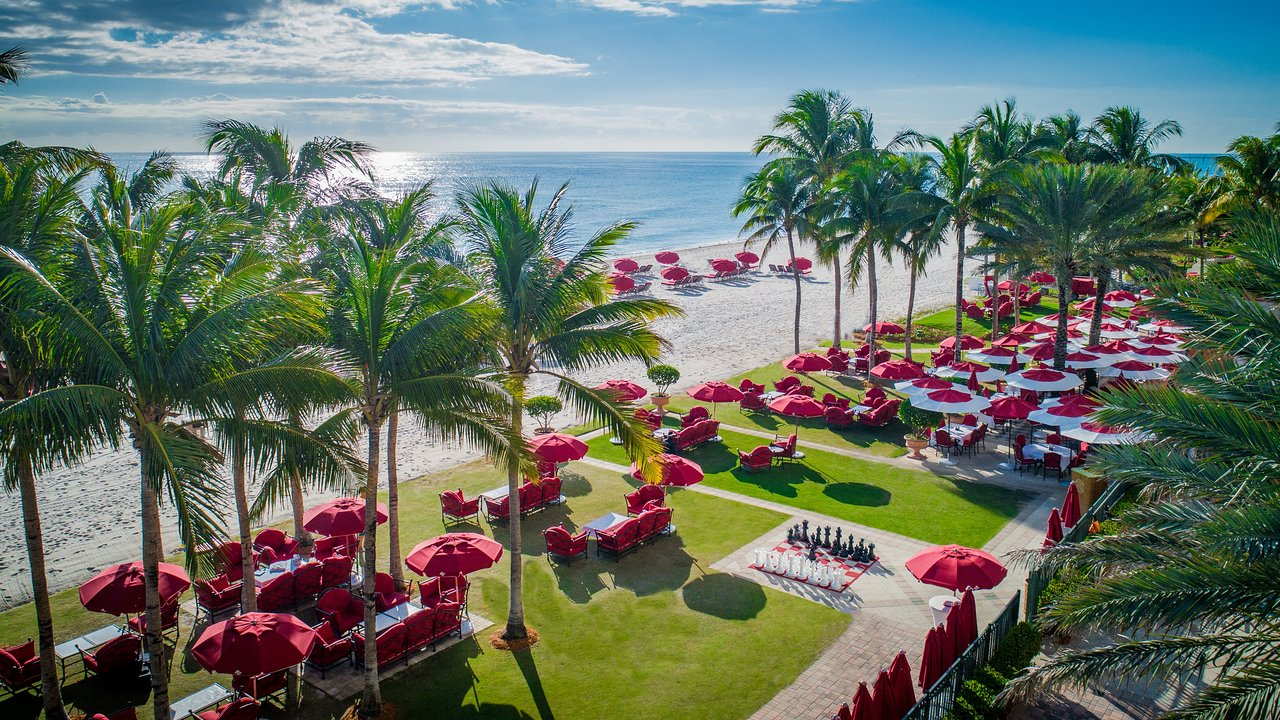 Lawn and beachfront of Florida resort with scattered red umbrellas and palm trees