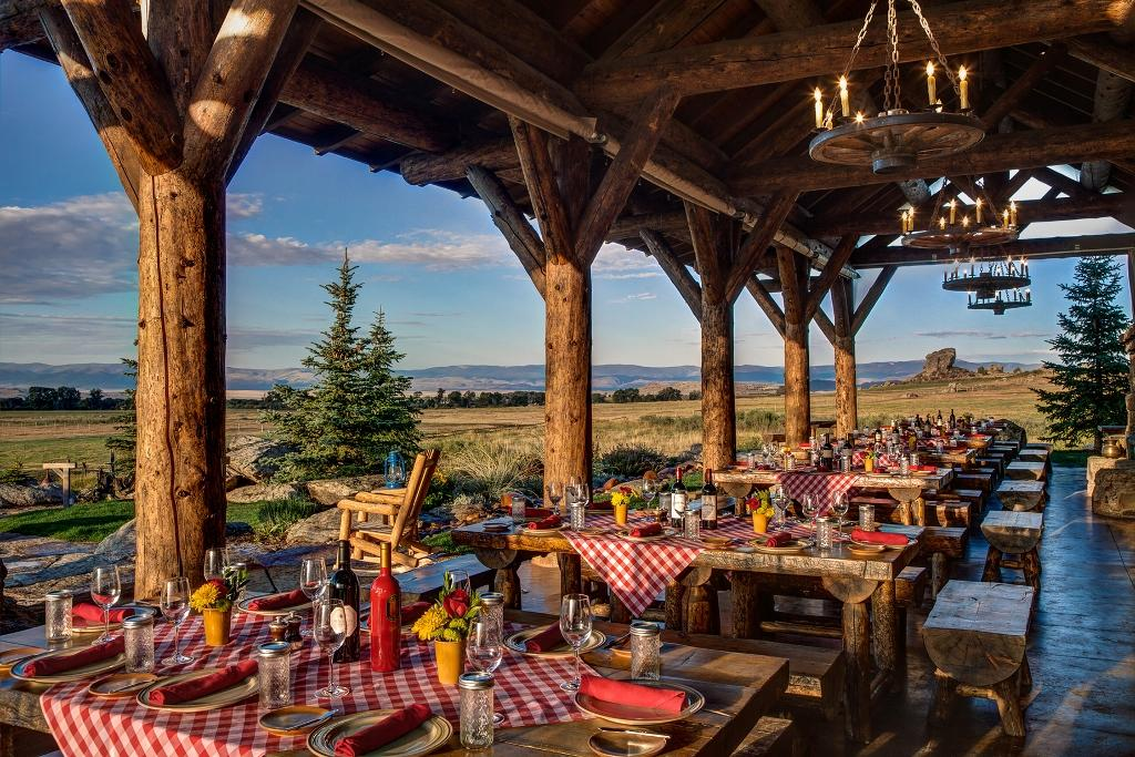 outdoor restaurant with red checkered tablecloths on wooden tables overlooking the plains.