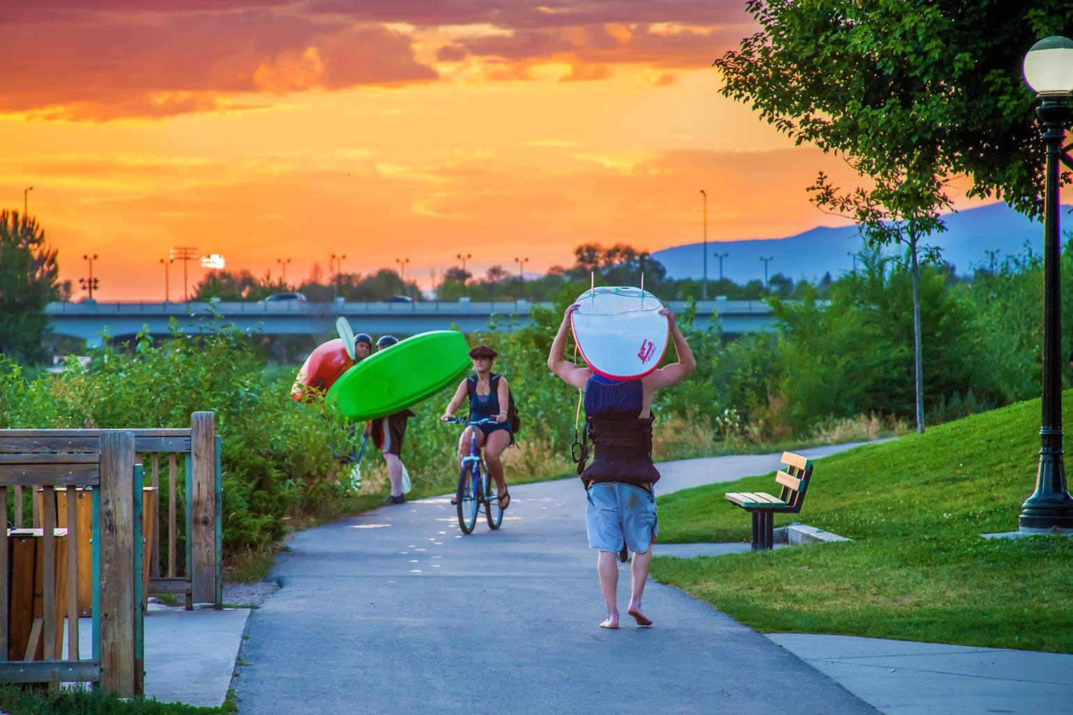 Surfers, kayakers and bikers share the riverfront walking trail in Downtown Missoula
