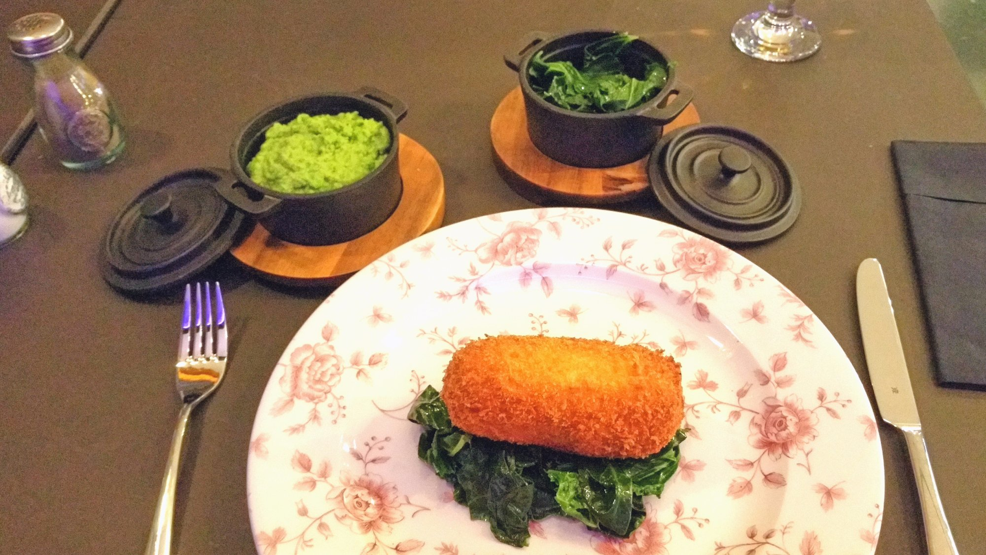 Chicken kiev with mushy peas and buttered greens sides