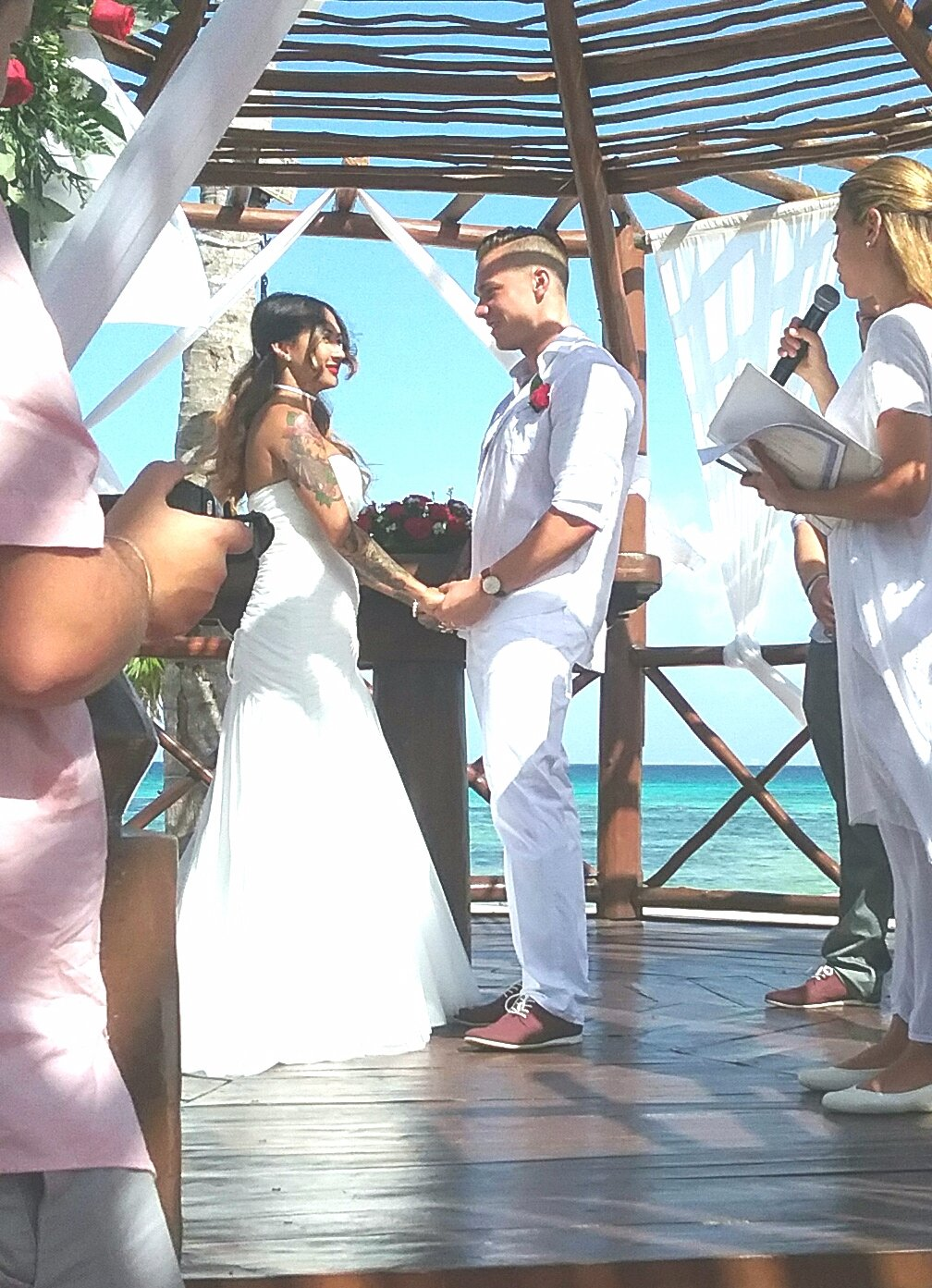 A beach wedding held under a wooden structure interlaced with red roses and white flimsy drapes