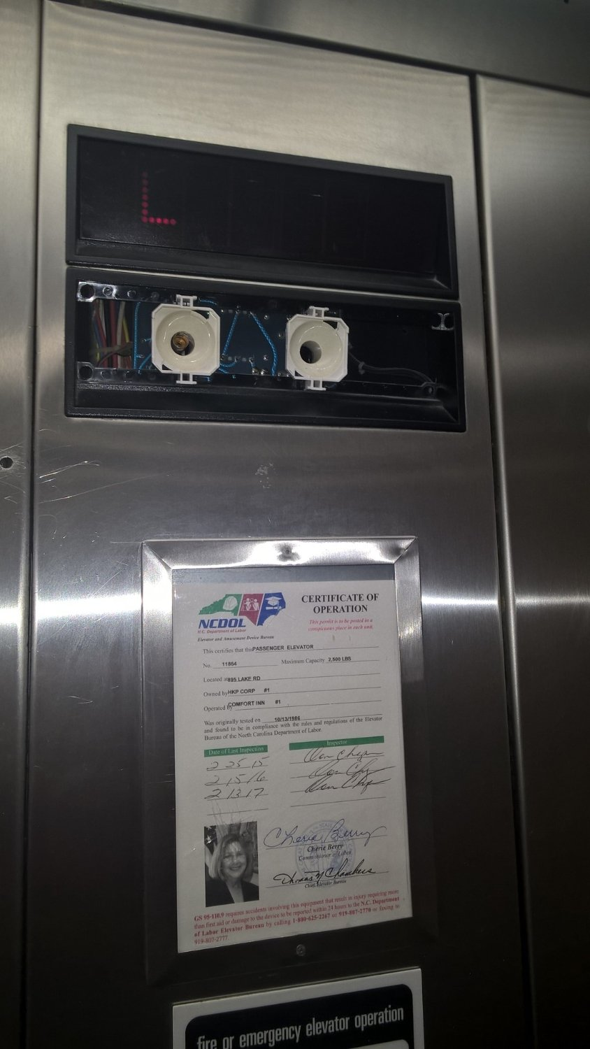 Elevator floor lights (ironically directly above the inspection sticker)