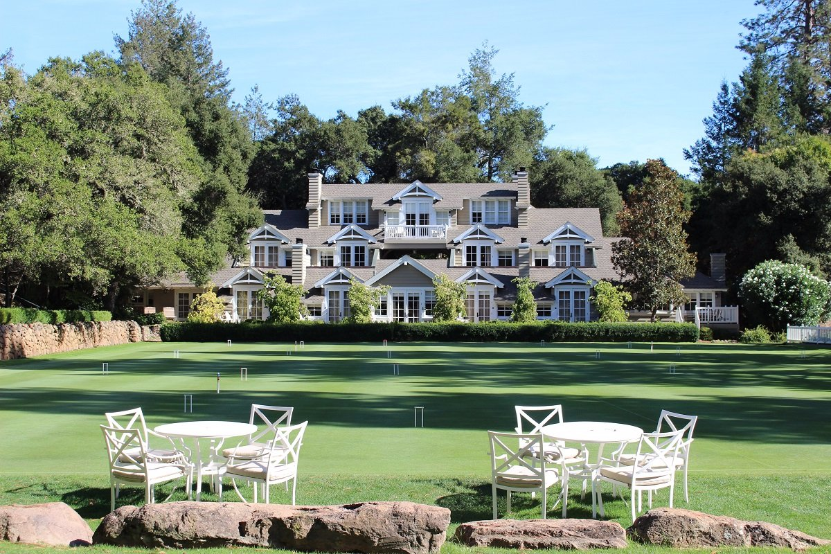 Spacious lawns with white tables and chairs and 3 story wood structure at the background