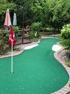 Newly Carpeted Green on hole 18 with white sand trips.