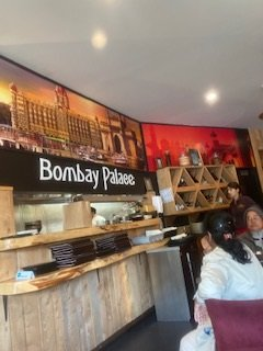 The board (Bombay Palace-Authentic Indian Food) attracts tourists, pedestrians, passengers travelling in bus or otherwise. This display is attractive and visible from distance.