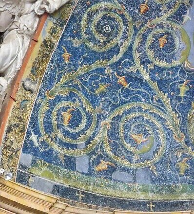 The 5th century mosaic is thought to be the oldest apse conch mosaic in Rome. It has weathered quite badly.The design is of green branching vine-scrolls on a blue background, with flowers and an ascending line of four little jewelled crosses within mandorlas in the centre.