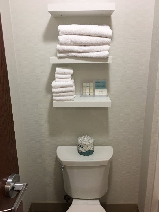Towels all in the bathroom above toilet