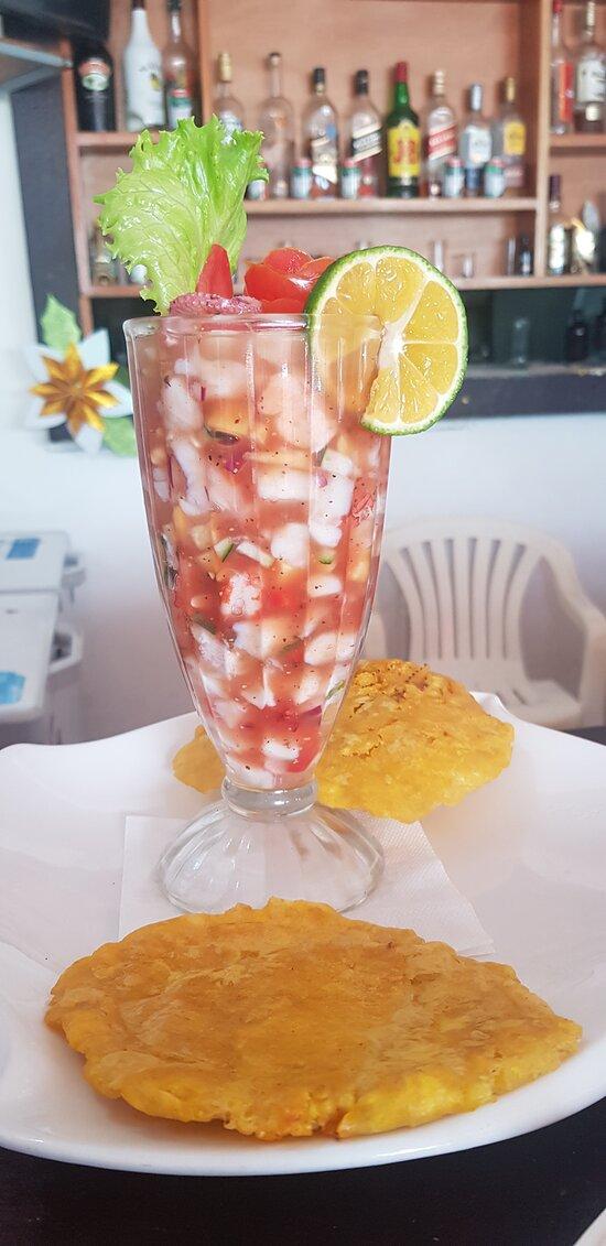 Sabroso Ceviche TYPICAL. Preparado con una exquisita combinación de frescos mariscos, pulpo, corvina, camarón Pink, pianguas, en una sala de tomate natural, pepino, plátano sancochado, especies, acompañado de crujientes patacones.