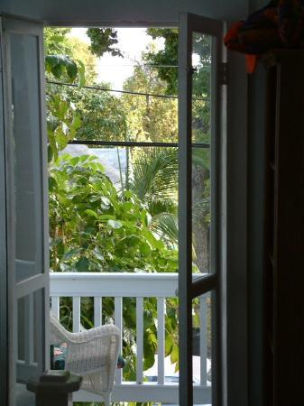 Seascape Tropical Inn: A view through the french doors to the upstairs porch in the front of the house.