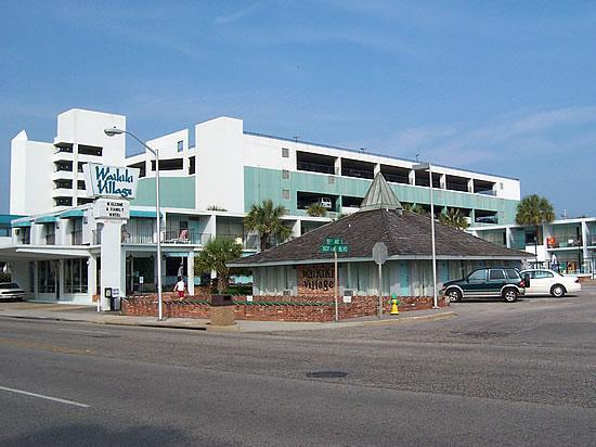 Waikiki Village Motel As Seen From The Street With Landmark Resort Parking Garage