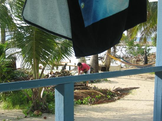 Tobacco Caye Lodge: Woman buring garbage outside cabin.