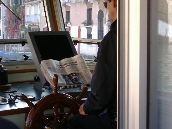 Venezia, Italia: Vaporetto No. 1 captain reading newspaper while cruising