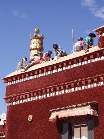 Lhasa, Kina: Tibetans painting the roof of the Potala Palace