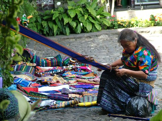 Antigua, Guatemala: Local woman weaving in the garden of the hotel
