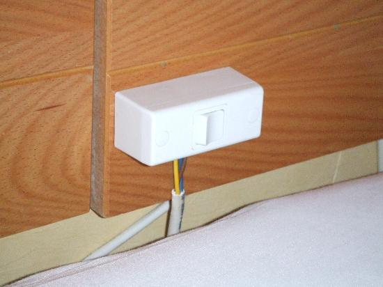 Summit Hotel: wires hanging loose behind bed