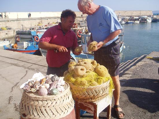 Ираклион, Греция: A fisherman is selling sponges from his boat -.