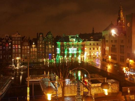 Dam Hotel: View at night - entrance to red light district is to right of the building with green lights
