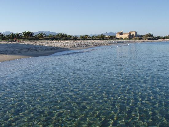 Sardinia, Italy: Pula town beach looking towards St Efisio church