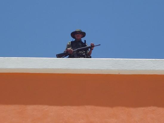 Guard with a gun on rooftop at Costa Maya