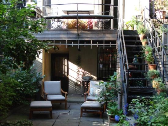 A Garden In Chelsea: Garden showing door to studio and staircase to host's quarters
