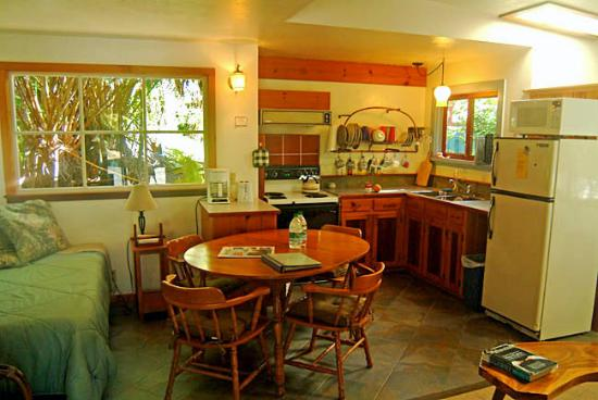 Volcano Guest House: The Cottage kitchen, dining area and living room. Couch is behind table at right.