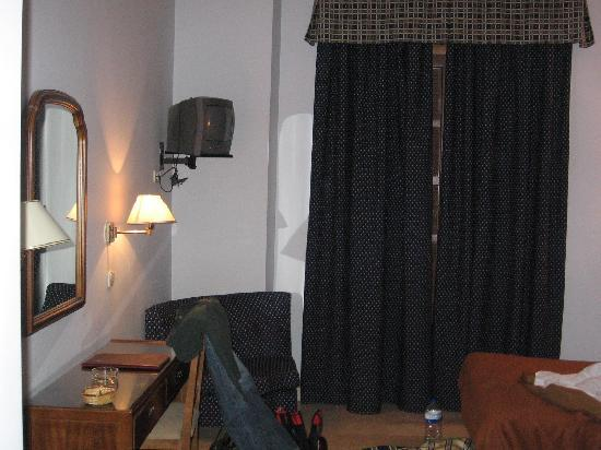 A view of the desk/vanity and the curtains, behind which is ...