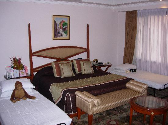 Hotel Vikram: room showing bed with 1 single either side