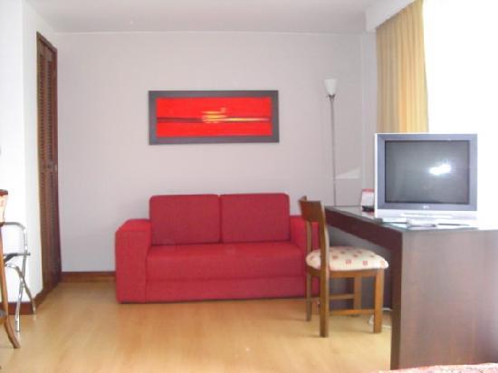 Leblon Suites Hotel: Canapé, bureau, TV