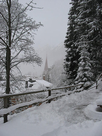 Bad Gastein, Austria: Snow covered trail with one of the church's in the background