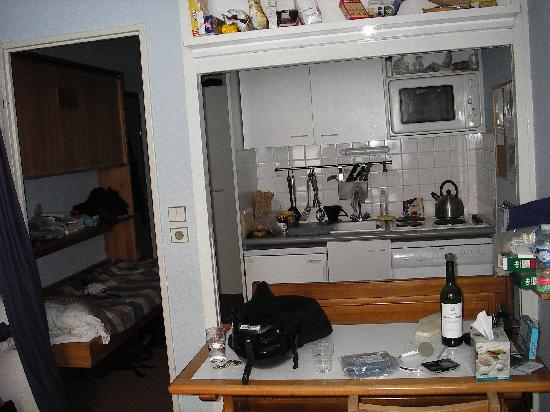 Table in living area opens to small kitchen halway bunk on left