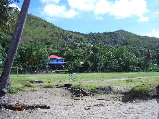 Mirage Beach Resort: The village cricket green - restaurant in the distance